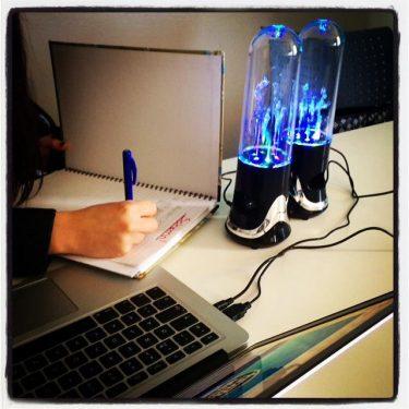 Hand skriver i häfte vid uppslagen laptop.