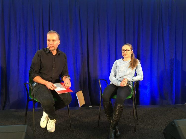 Man intervjuar elev på scen.