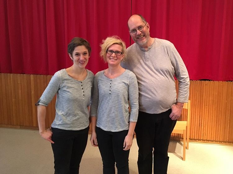 Tre skådespelare framför ett rött draperi