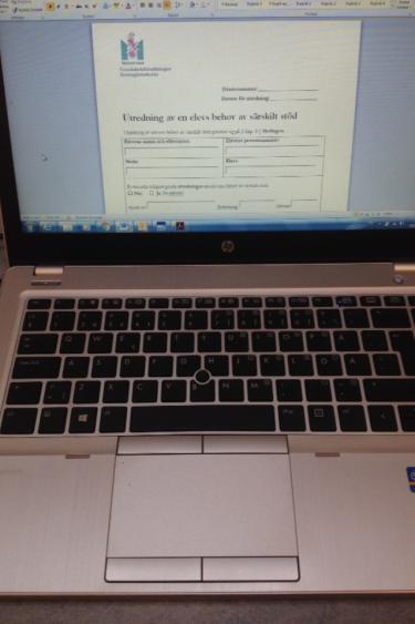 Dokument är öppet på uppfälld laptop.
