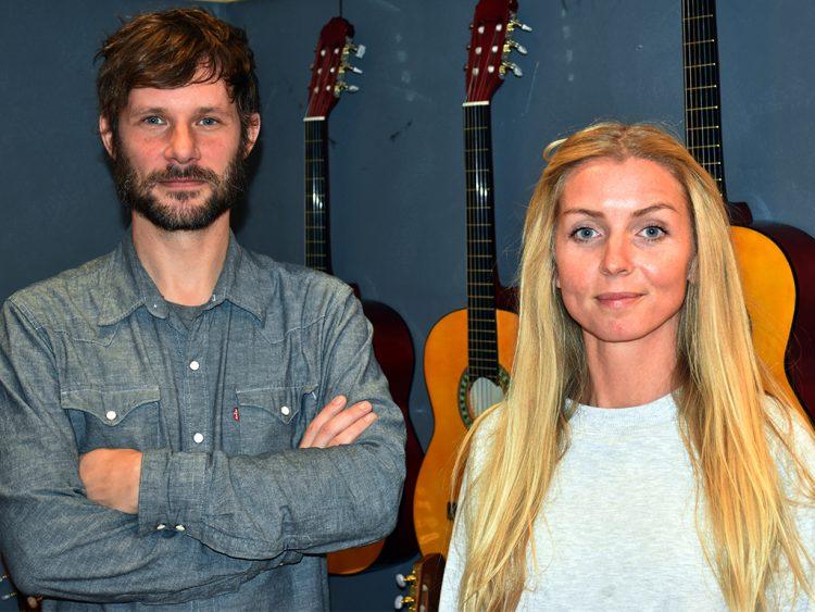 Linus och Isis framför gitarrer som hänger på väggen.
