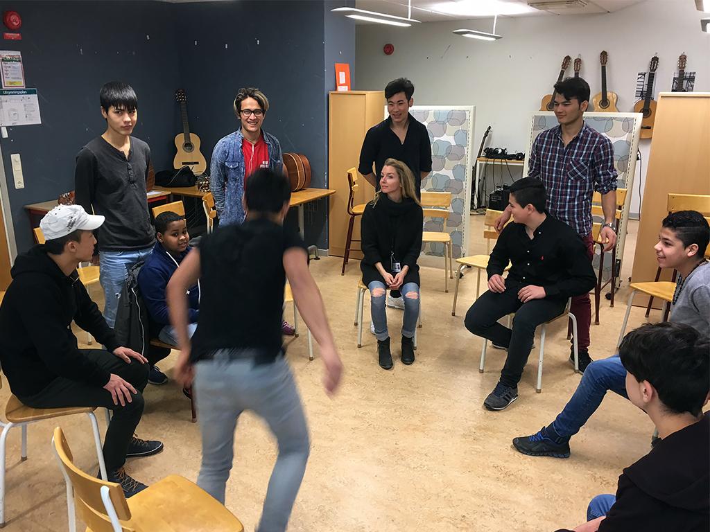 Elever sitter i ring i musiksal.