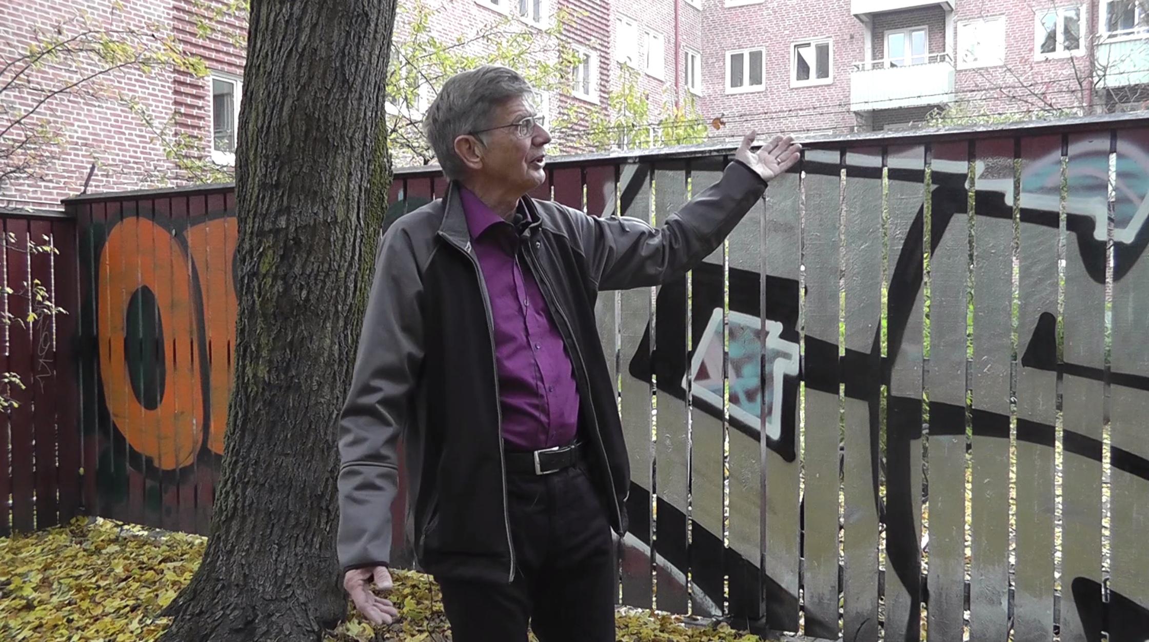 Bertil framför plank med grafitti.