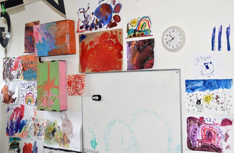 Målningar av barn uppsatta på vägg.