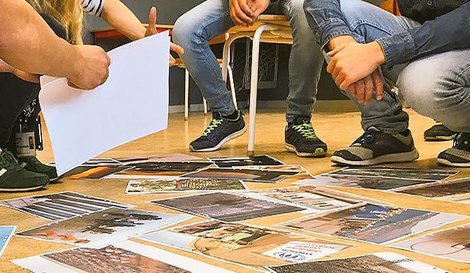 Bilder ligger på golvet framför elevernas fötter.