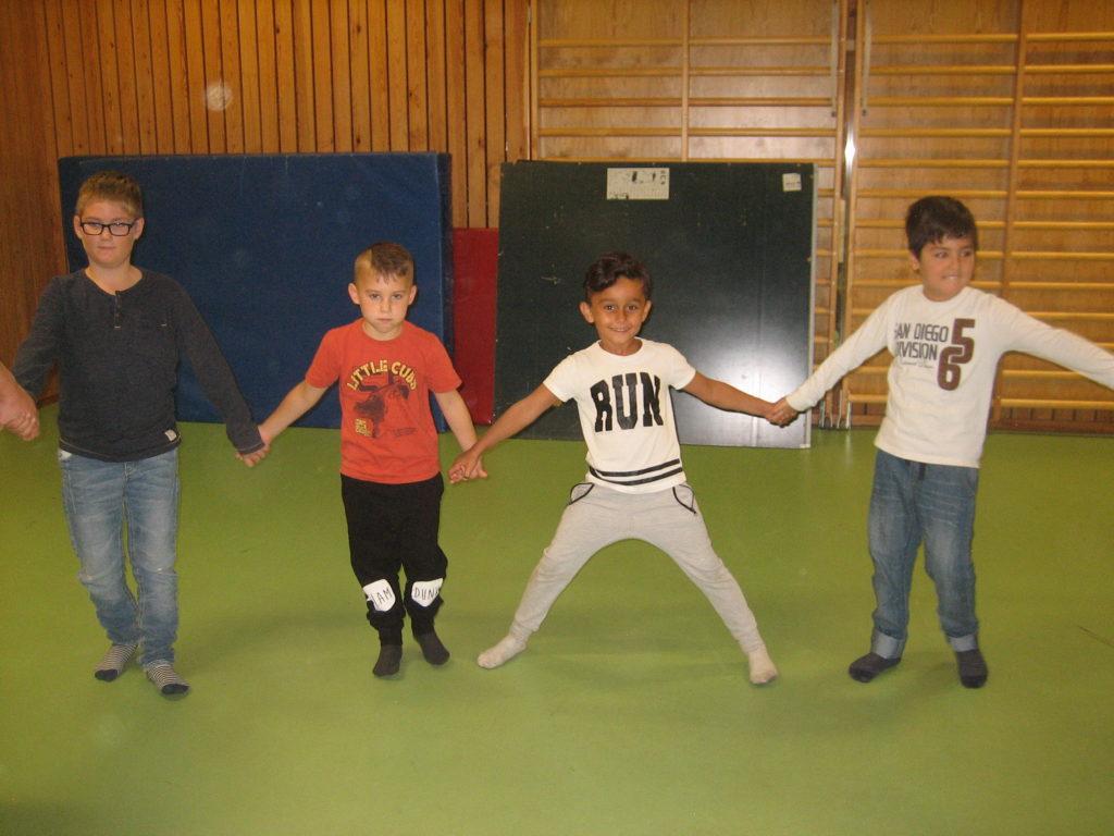 Fyra barn håller varandra i händerna.