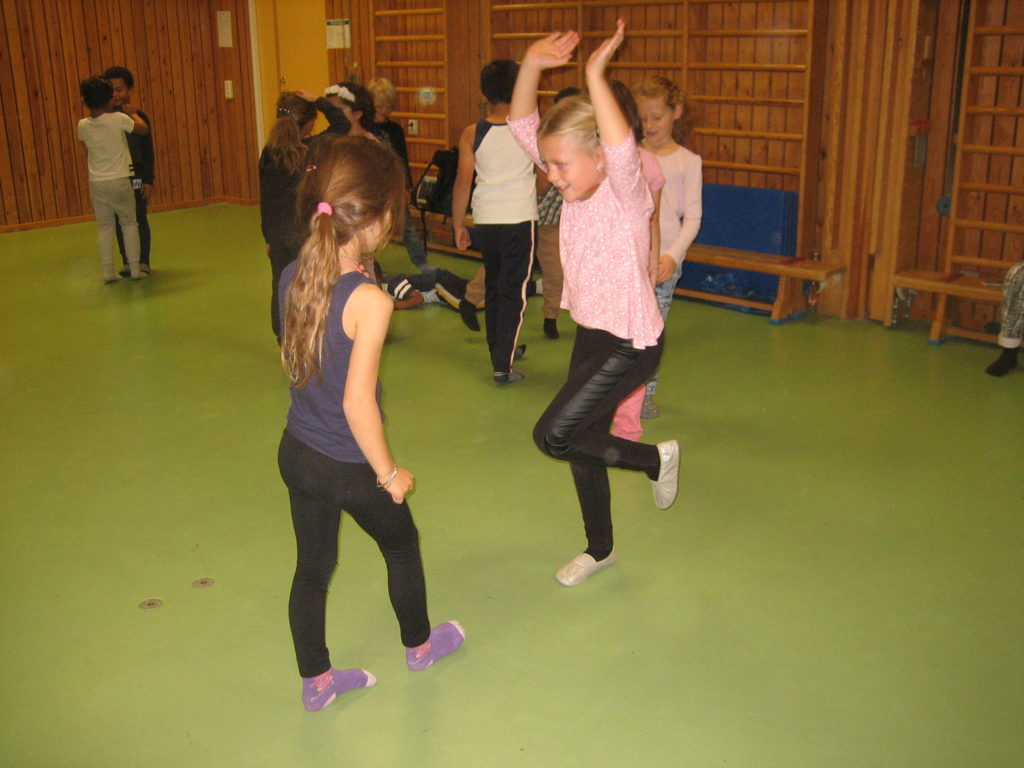 Två elever dansar i gympasal.