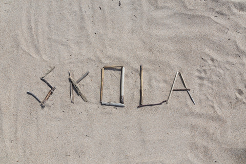 Skola står skrivet i sand.