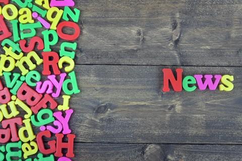Ordet news bildas av kylskåpsmagneter.