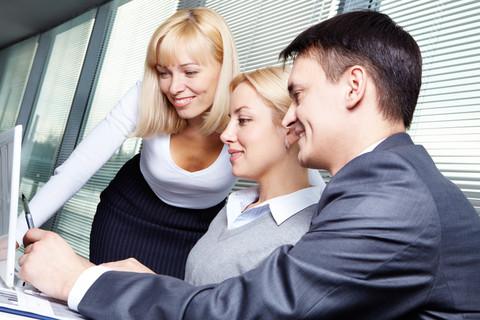 Tre personer tittar in i uppfälld laptop.