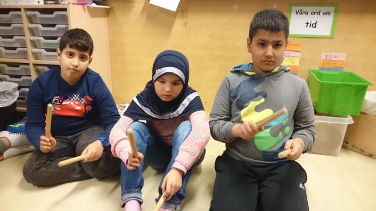 Elever spelar på träpinnar.