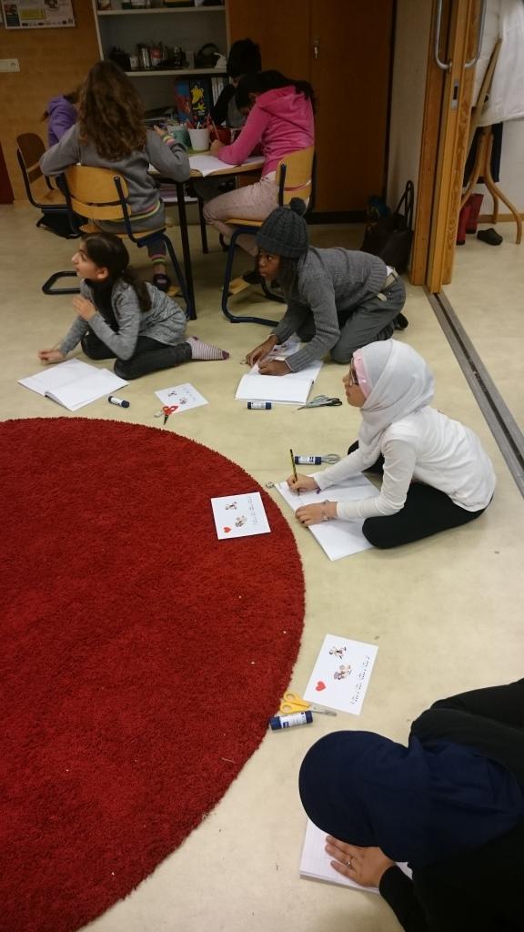 Elever sitter på golv och jobbar.