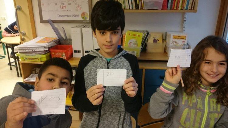 Tre barn håller på lappar där det står yes och no.