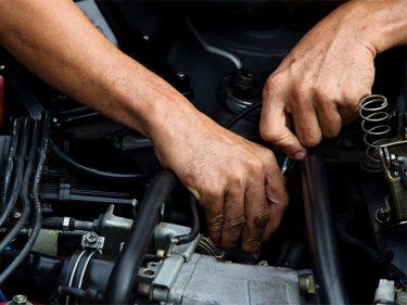 Händer mekar med motor.