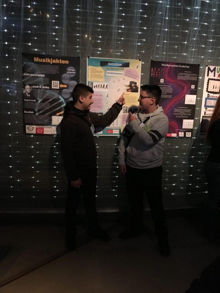 Två elever framför affisch.
