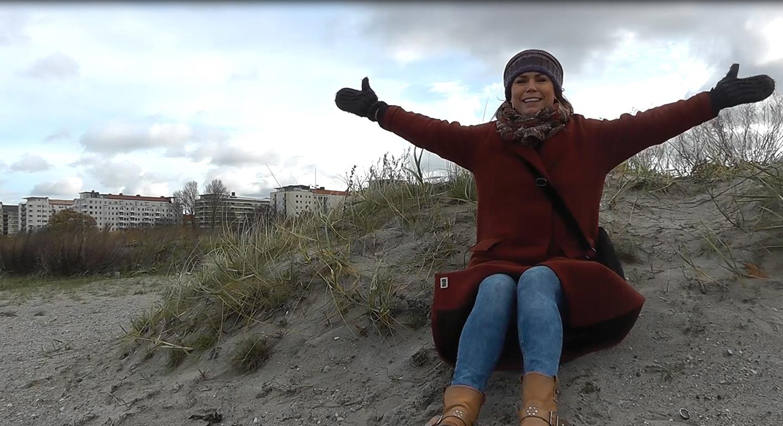 Kvinna sitter på strand och slår ut med armarna.