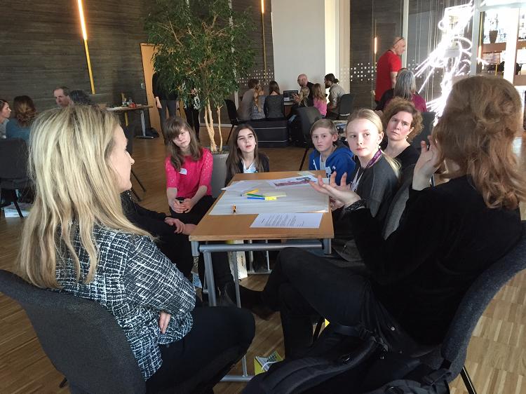Grupper av barn och vuxna sitter runt bord.