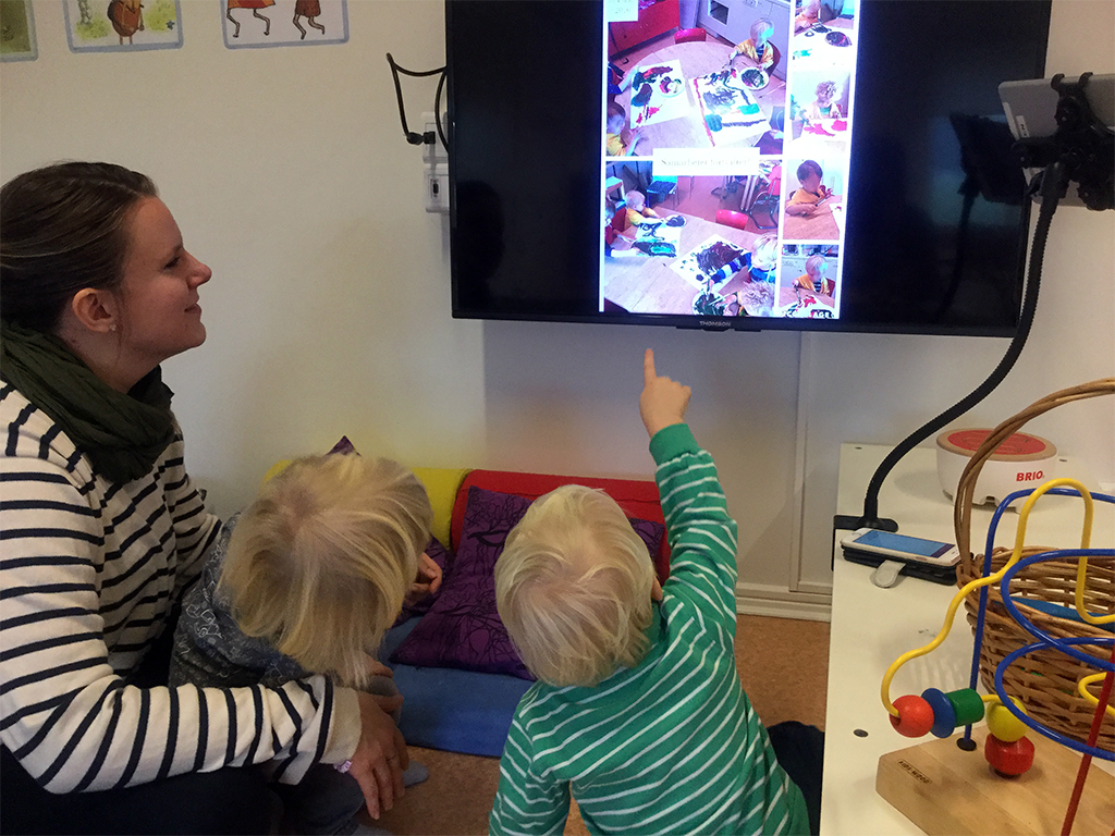 Barn tittar på bilder på tv.