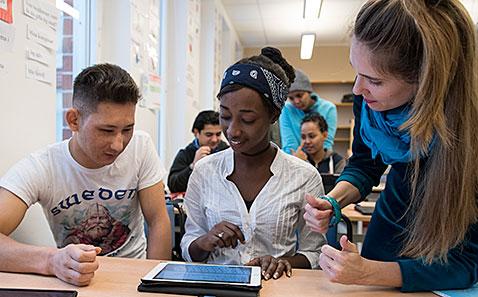 Två elever jobbar med ipad och kvinna lutar sig fram för att hjälpa.