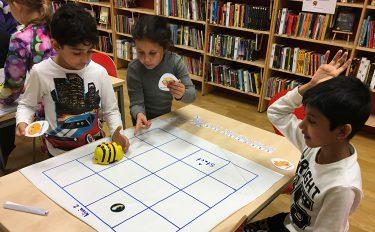Barn programmerar beebots att gå i ett rutmönster.
