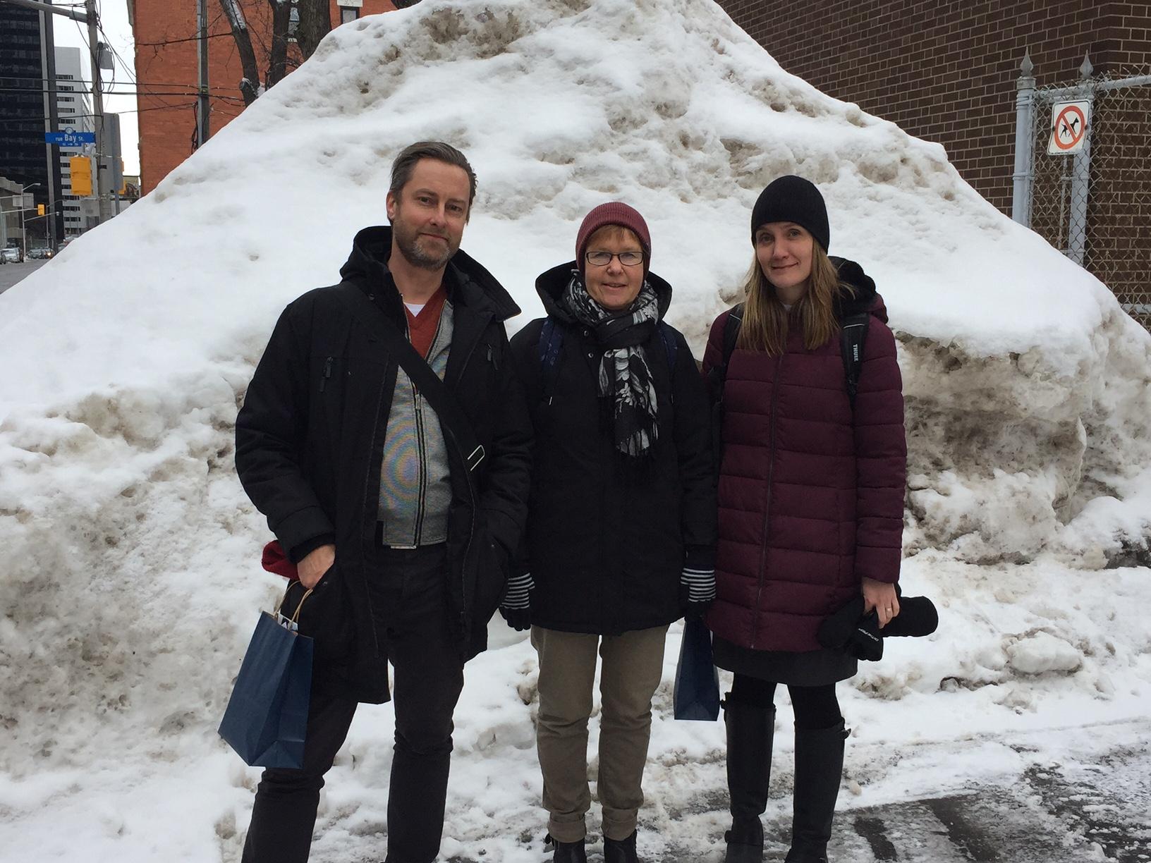 Tre personer framför snöhög.