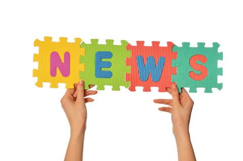 News står på pusselmattor som hålls upp av händer.