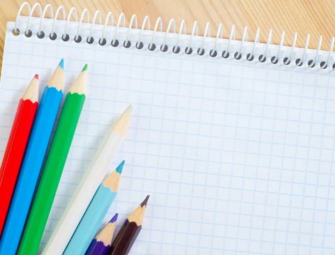 Pennor ligger på rutat papper.