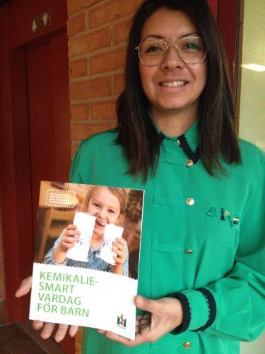 Matilde Törnqvist håller upp broschyr om kemikaliesmart vardag för barn.