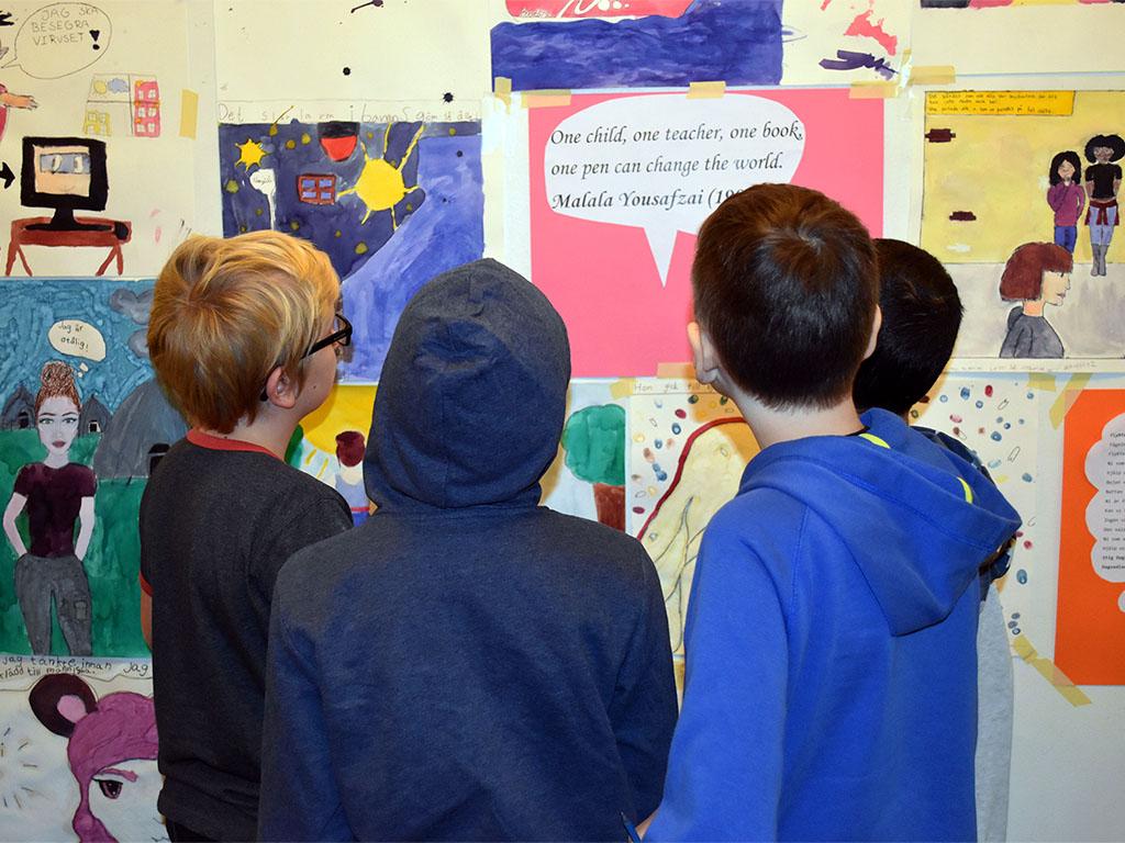 Elever tittar på teckningar som sitter uppsatta på vägg.