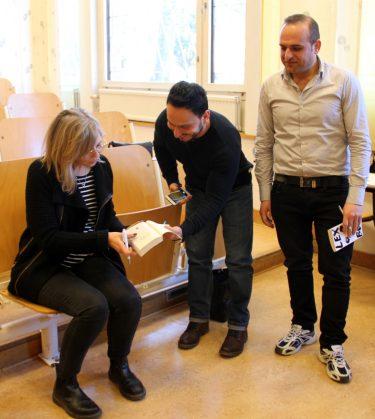 Två män håller fram böcker för att få autograf från Sara Kadefors.