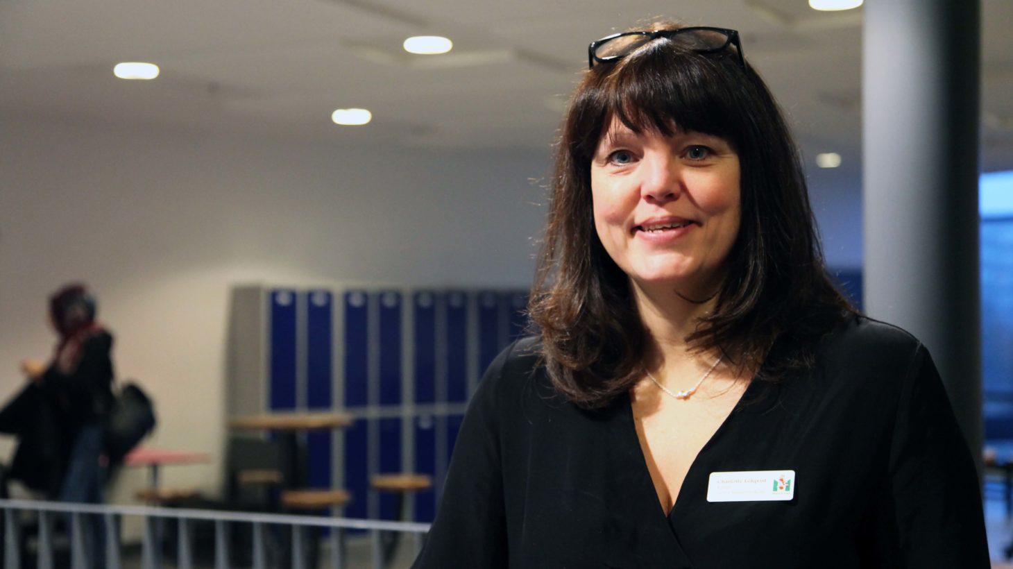 Charlotte Löfqvist står i kapprum på skola.