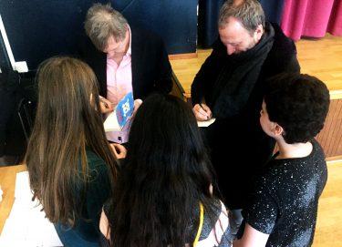 Anders och Sören skriver autografer till tre barn.