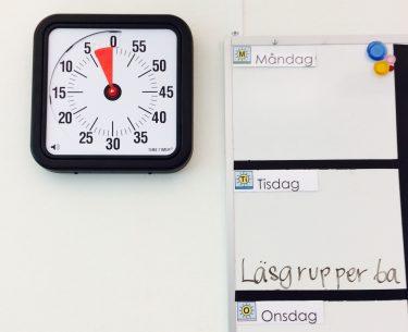 En timer bredvid whiteboard där dagens schema står.