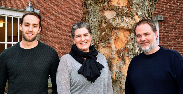 Tre pedagoger framför skolbyggnad.