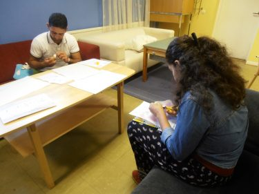 Två personer sitter vid bord och klipper och tejpar.