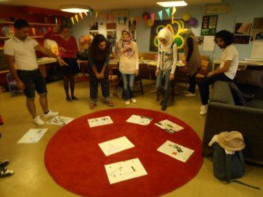 Papper ligger på röd matta och pedagoger står runt.