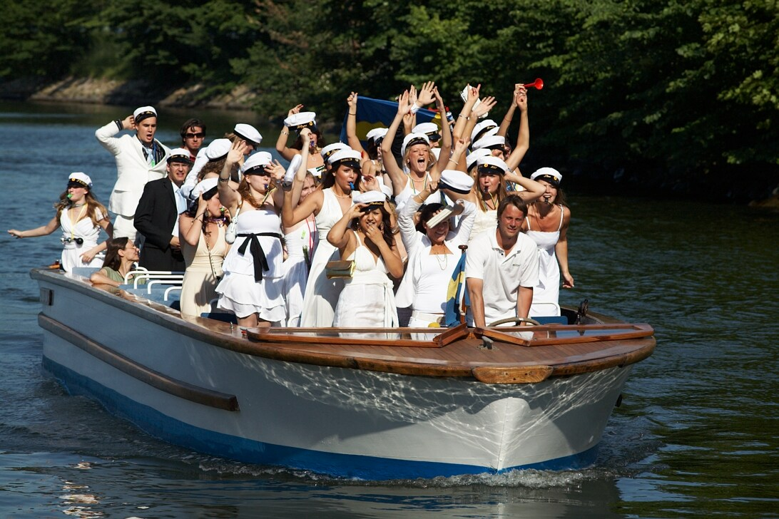 Studenter står på båt i kanal.