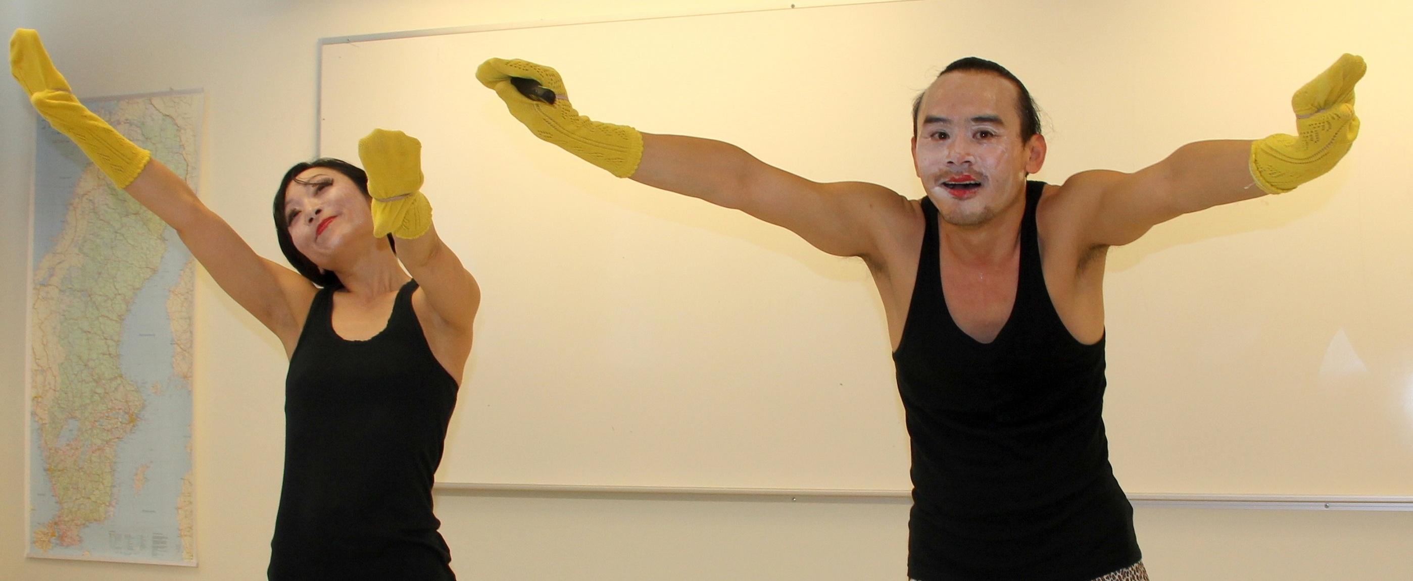 Kvinna och man håller ut händerna som har gula handskar.