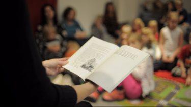 Pedagog håller i uppslagen bok.