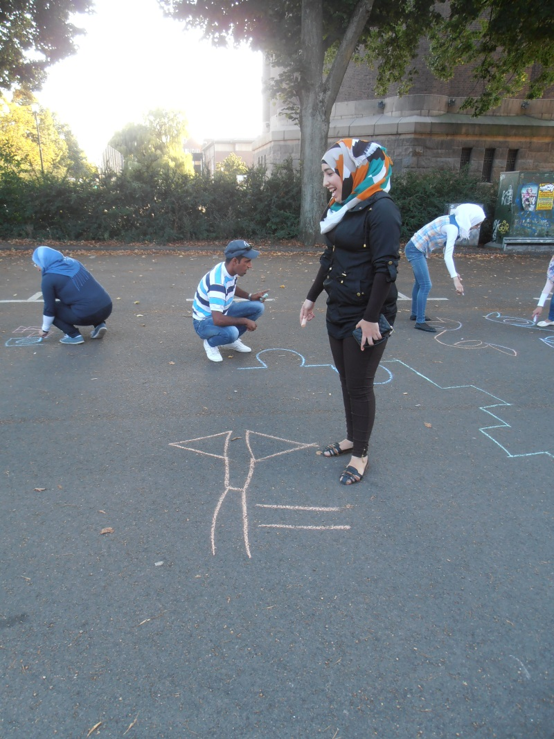 Personer målar figurer på asfalten med krita.