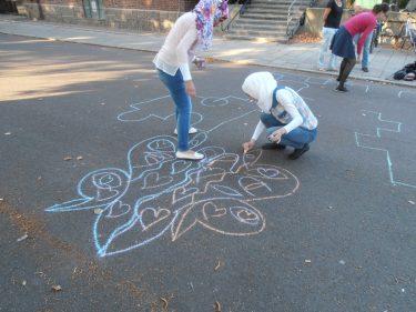 Två flickor målar mönster på gatan med krita.
