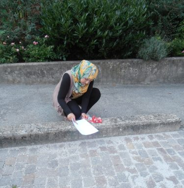 Flicka hukar sig vid trottoarkant och skriver på papper.