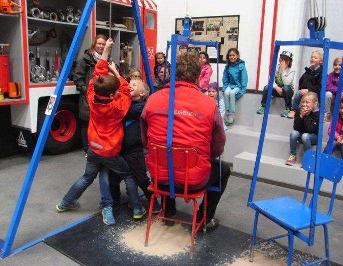 Barn försöker dra upp vuxen som sitter på stol.