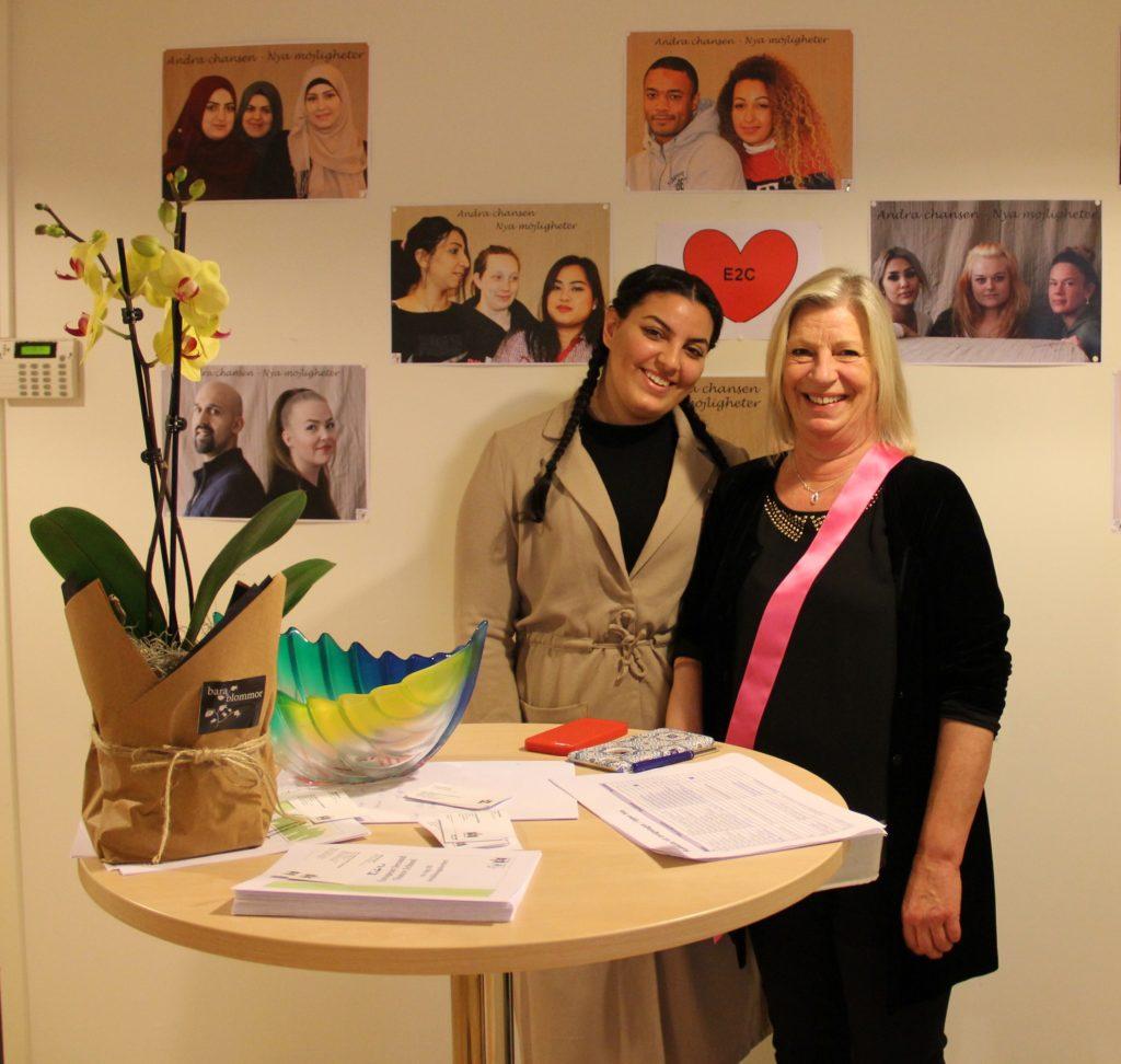Hiba och Susanne Ramberg står vid bord med blomma.