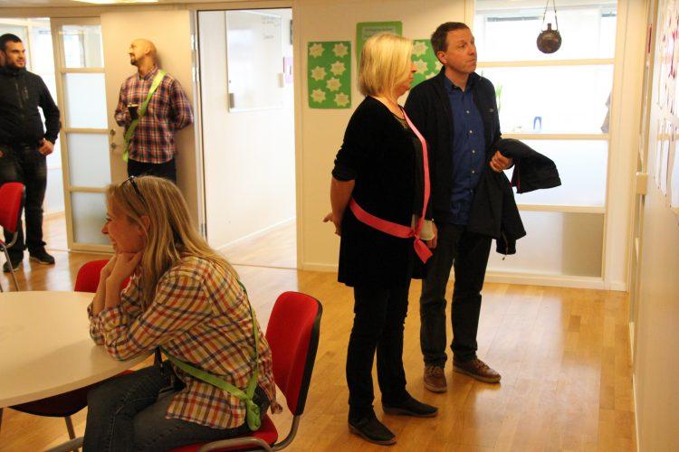 Två personer står och tittar på utställning på vägg.