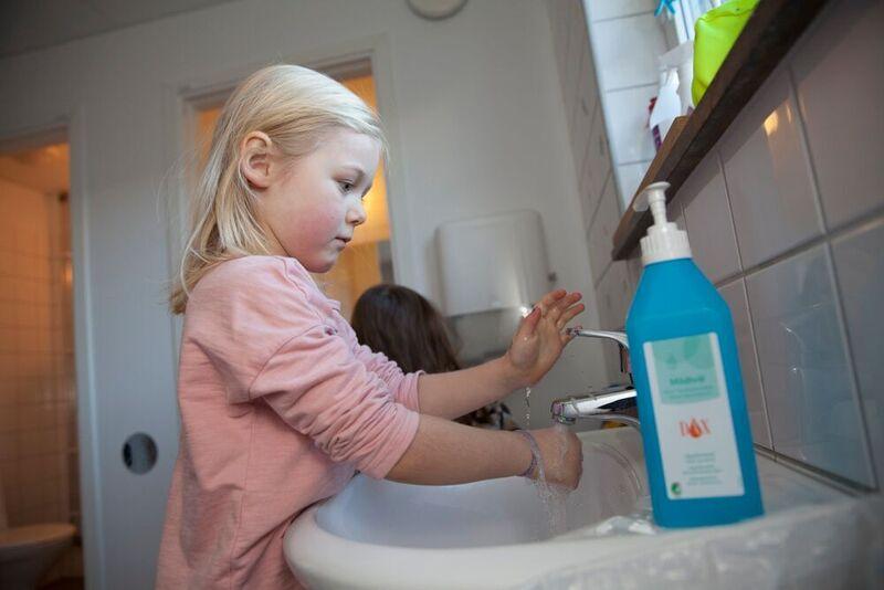 Flicka tvättar händerna i handfat.