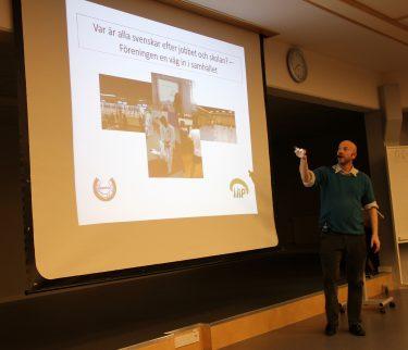 Man föreläser framför projicerad presentation.
