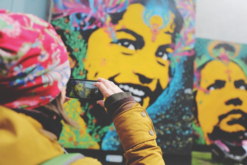 Barn fotograferar graffitivägg.