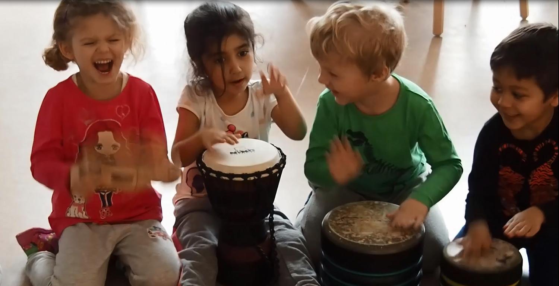 Fyra bar trummar och ser glada ut.