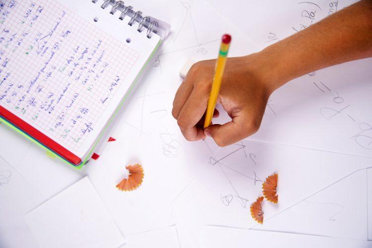 Hand håller i penna och skriver.